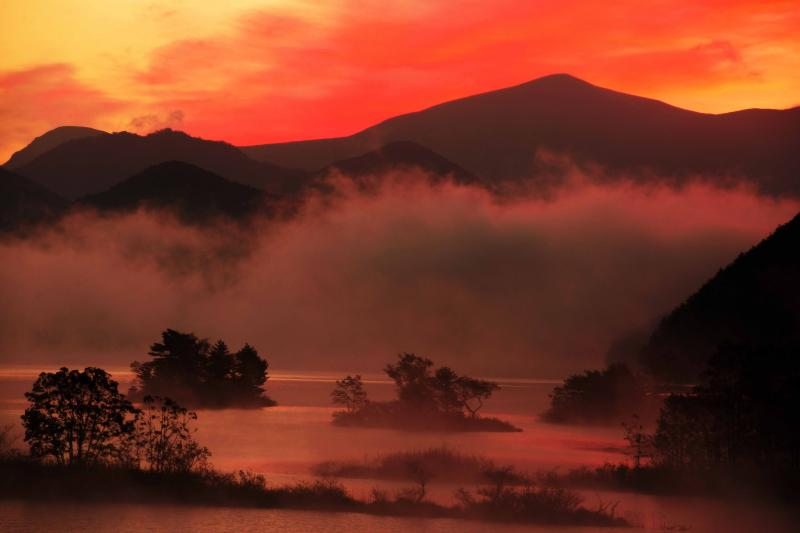 [ 真っ赤に燃える浮島 ]  朝焼けが湖面を真っ赤に染め、シルエットになった島々が浮かび上がります。