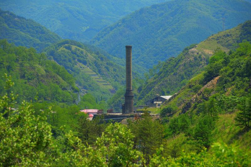 [ 銅親水公園から見た大煙突 ]  銅親水公園からは山の谷にそびえる大煙突の姿が。