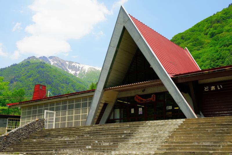 土合駅の三角屋根と残雪の山 | 谷川岳登山の拠点となっている上越線の土合駅。三角の赤い屋根が印象的。
