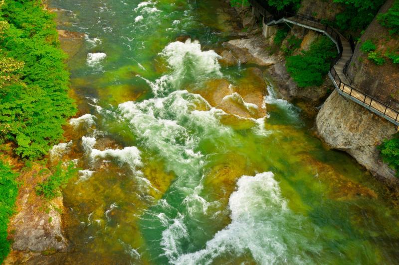 [ 諏訪峡遊歩道と利根川の流れ ]  諏訪峡大橋から利根川を見下ろすと、遊歩道と白波を立てる激流が見えます。グリーンの美しい水の流れが爽快な場所です。