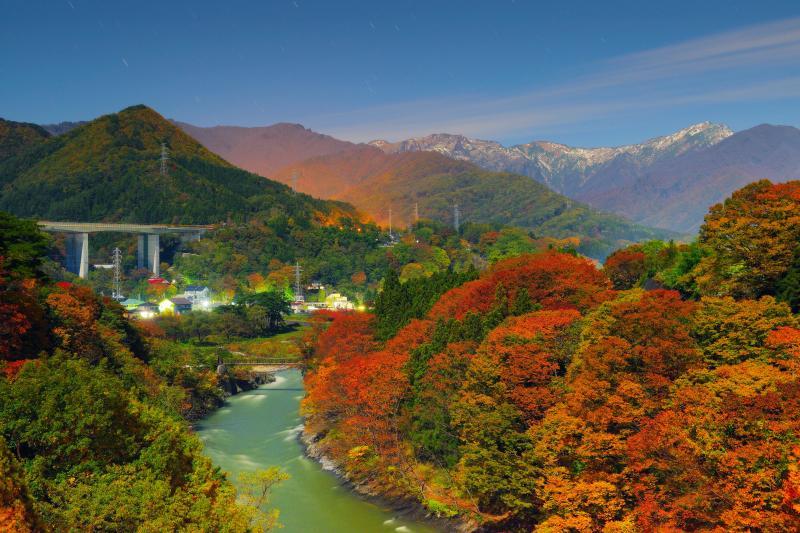 [ 諏訪峡の紅葉と谷川岳 ]  紅葉と月明かりが重なり、真夜中の諏訪峡は色鮮やかな絶景に。谷川岳の上空を雲が流れていきました。