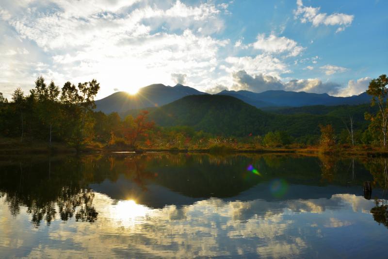 [ 乗鞍高原の夕暮れ ]  乗鞍岳に夕日が沈んでいきます。夕日と雲が水面に映り、逆光で紅葉した木々の葉が美しく輝いていました。