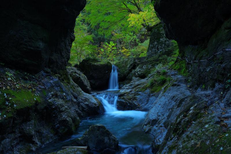 [ 岩窓 ]  両岸からは大きな岩が迫り出しており、中央に見える滝や木々の緑は窓の中にあるアートのよう。