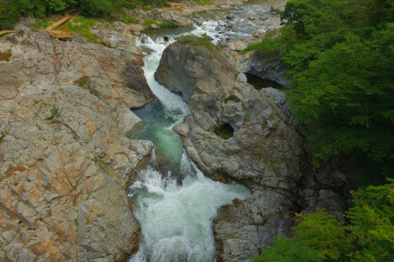[ 峡谷俯瞰 ]  橋の上から展望台と巨大な岩を望む。丸い穴の空いた大きな岩は生き物のよう。
