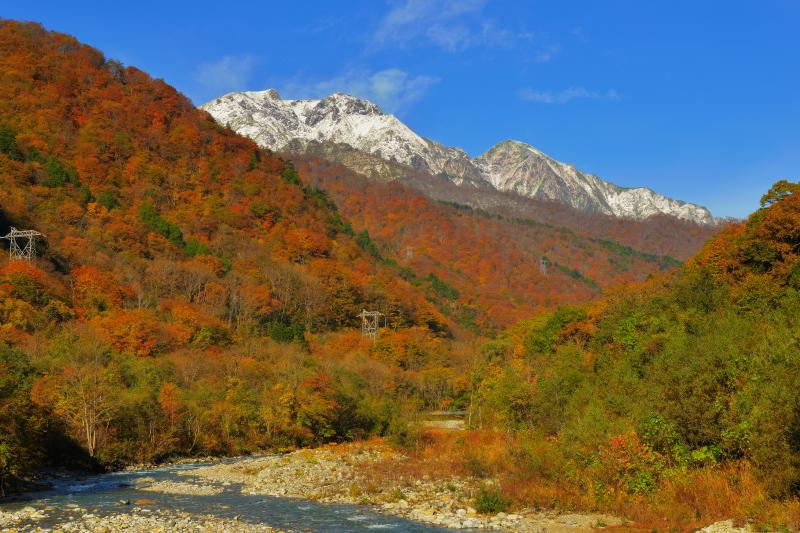 [ 谷川岳三段紅葉 ]  蛇行する湯檜曽川の流れ、一面に広がる紅葉、雪化粧した谷川連峰が美しい。
