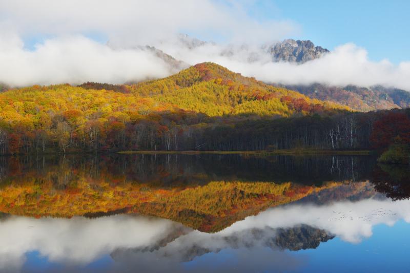 [ 紅葉シンメトリー ]  紅葉の木々と空そして流れ行く雲が鏡のように水面に映り込んでいました。