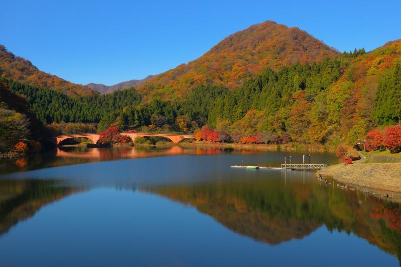 [ 紅葉の山々と碓氷湖 ]  対岸にはレンガ調の橋があり、歴史を感じる湖になっています。めがね橋はこのすぐ上側にあります。