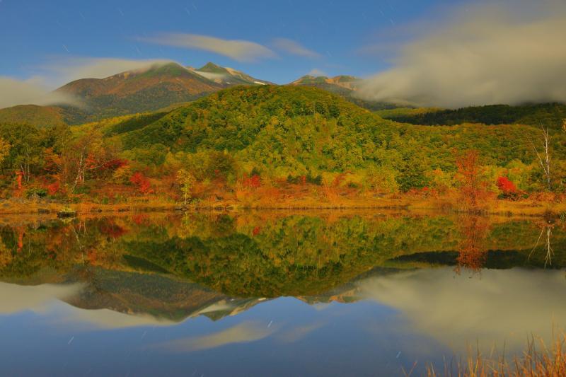月光乗鞍 紅葉シンメトリー | 月明かりに照らされたまいめの池。乗鞍岳を流れる雲、空を舞う星たちが穏やかな水面に映り込んでいました。