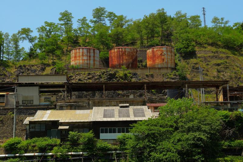 [ 3つの寂れたタンク ]  本山精錬所跡の3つのタンク。タンク下には駅のホームのような建物が見えます。