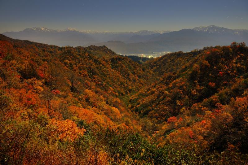 [ 紅葉谷 ]  深い谷を埋め尽くす紅葉。魚沼の街明かりと初冠雪した越後の峰々の絶景が広がっていました。