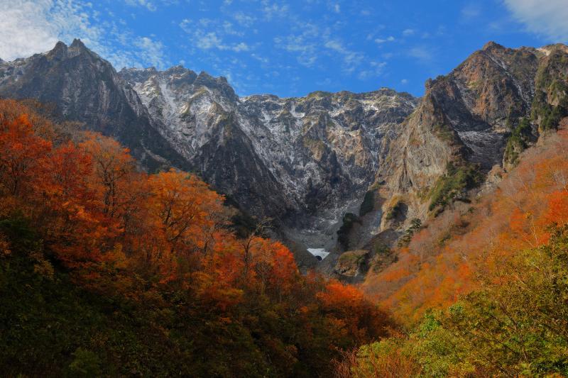 [ 一ノ倉沢 三段紅葉 ]  紅葉に包まれた一ノ倉沢。雪と黒い岩のコントラストでより迫力ある姿に。到着時、谷川岳に雲がかかっていましたが、撮影中に青空になりました。