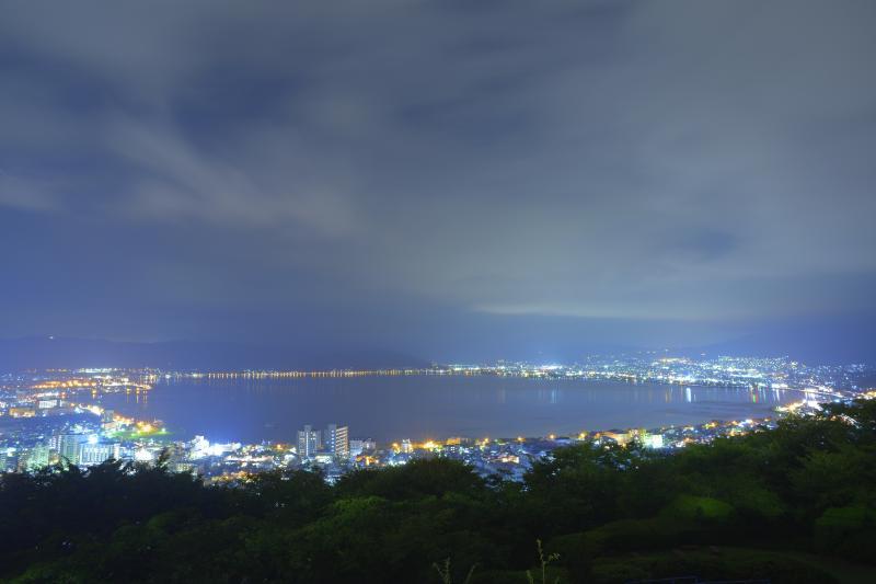 [ 真夜中の諏訪湖 ]  公園先端の柵付近から撮影しました。流れる雲が幻想的な夜でした。