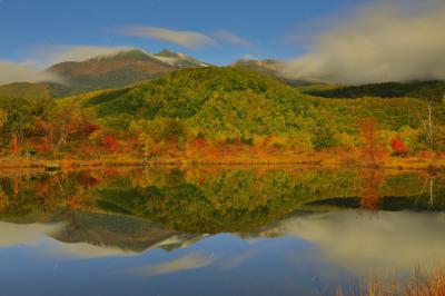月光乗鞍 紅葉シンメトリー| 月明かりに照らされたまいめの池。乗鞍岳を流れる雲、空を舞う星たちが穏やかな水面に映り込んでいました。