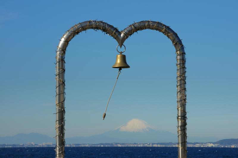 幸せの鐘と富士| 海岸沿いの駐車場にある幸せの鐘。フレームの中に富士山を入れることができ、観光スポットとして人気の場所です。