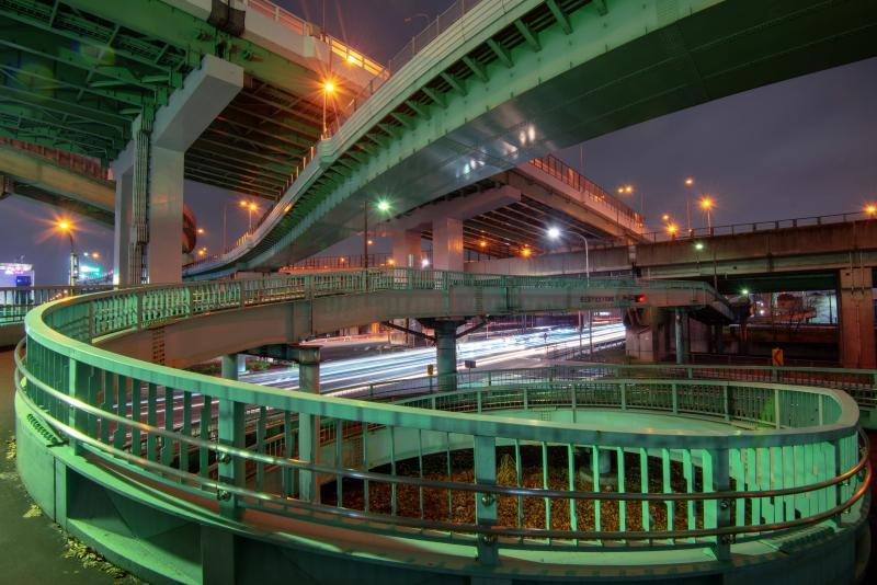 歩道橋ループ| とぐろを巻く歩道橋から交差する高速道路を見上げて撮影しました。車と人が交差するジャンクションの夜景。