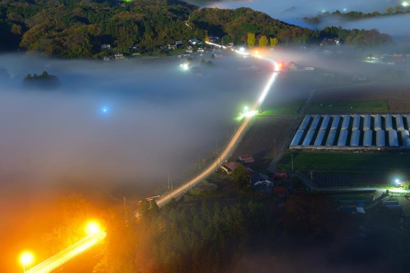 [ 雲海レーザービーム ]  早朝に雲海が湧き始め、その中を走る車の光跡が幻想的でした。夜明け前は雲海と街明かり、車の光跡のコラボレーションや星撮影を楽しむことができます。