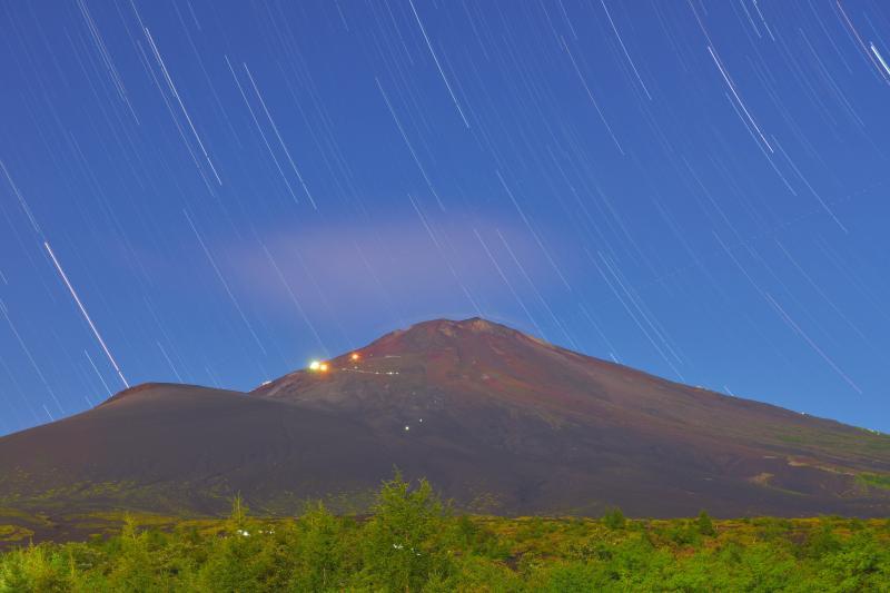 山小屋の灯と星| 月明かりに照らされた真夏の富士山。山小屋の灯りと登山客のヘッドランプが見えます。空には星が輝いていました。