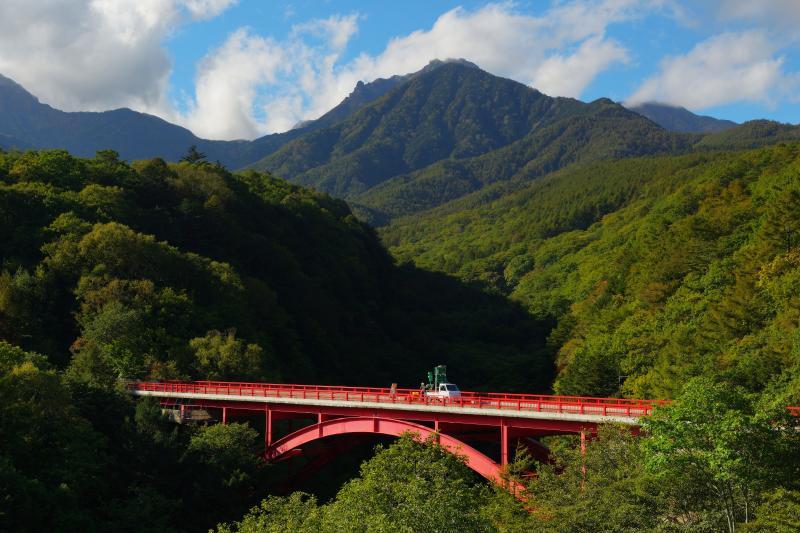 [ 赤い橋と八ヶ岳 ]  初秋の東沢大橋と八ヶ岳。青い空にモクモクと雲が湧いてきました。