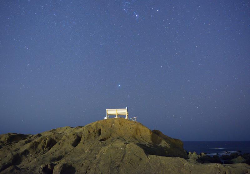 白いベンチと星空| 天の川撮影で人気の野島崎。大きな岩の上に白いベンチがあるという不思議な風景。