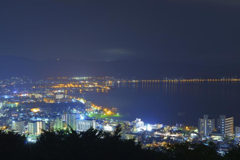 [ 諏訪湖と街明かり ]  立石公園から左方向を撮影。湖岸のビル・マンションなどの灯りが美しい。