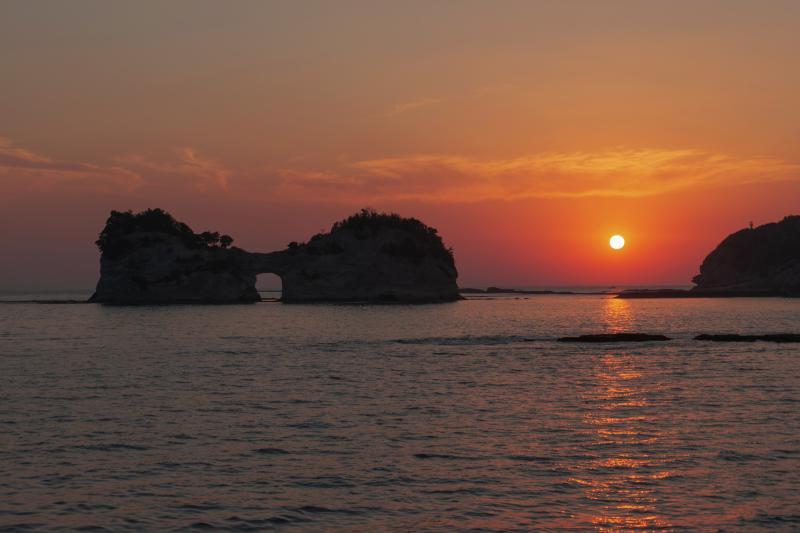 円月島夕日| 円月島の奥に夕日が静かに沈んでいきました。