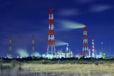 風になびく煙突の煙| 広い空き地の先には巨大な煙突群が見えました。紅白の煙突とシルバーに輝く工場夜景が美しい。