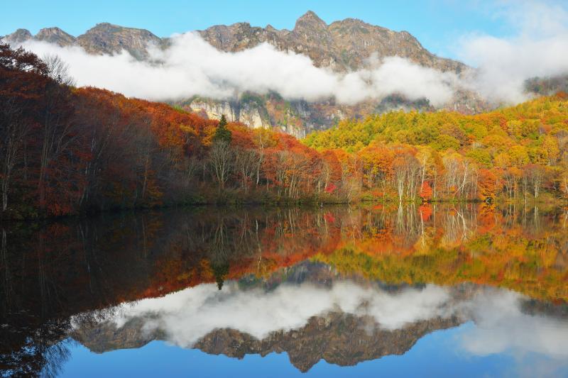 戸隠連峰雲景色 | 紅葉と戸隠連峰の間を、雲が横断しています。