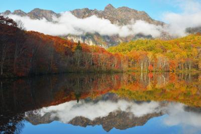戸隠連峰雲景色| 紅葉と戸隠連峰の間を、雲が横断しています。
