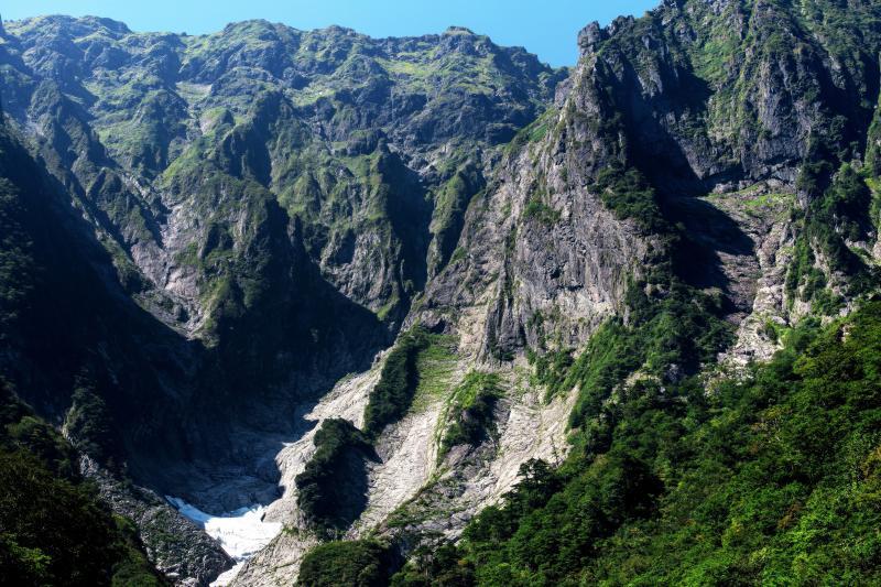 [ 大迫力の一ノ倉沢 ]  絶壁の間に雪渓が見えます。垂直に近い大きな壁がロッククライミングで有名な衝立岩。