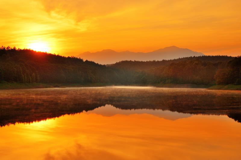 [ 新区画ダム ]  朝の光に照らされて湖面に漂う薄霧が印象的でした。遠景は旭岳。