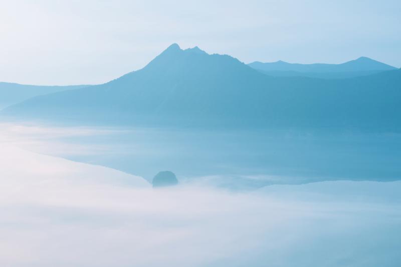 [ 霧の摩周湖 ]  うっすらと浮かび上がるカムイヌプリとカムイシュ島。霧に包まれた早朝の摩周湖は幻想的でした。