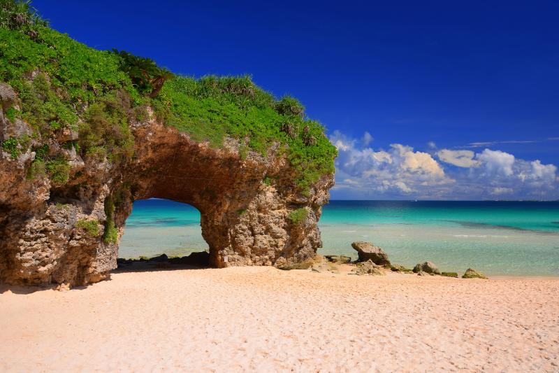 隆起サンゴのトンネル| カルスト状の隆起サンゴが白い砂浜にアクセントを与えています。