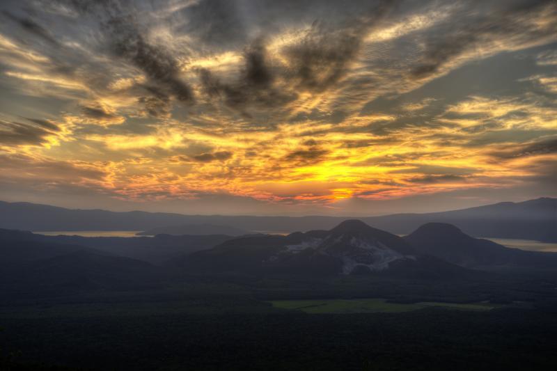 [ 夕刻の硫黄山 ]  摩周湖第三展望台から見た夕刻の硫黄山。後ろに屈斜路湖が見えます。西から迫ってくる雲が印象的でした。