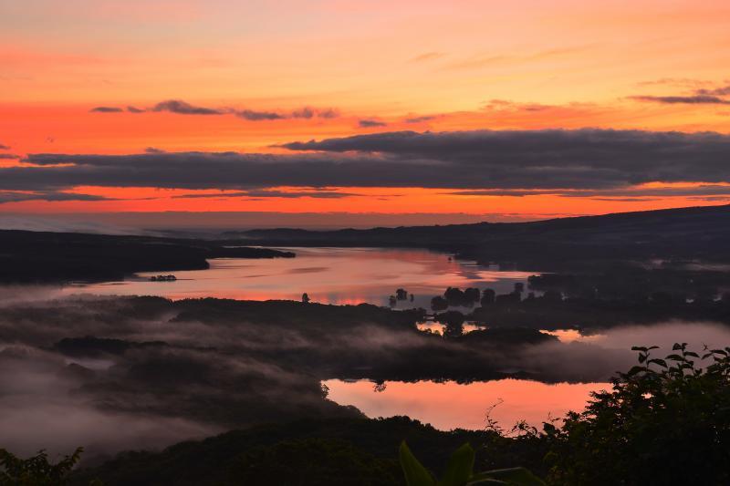 [ 日暮山の夜明け ]  流れる霧と茜に染まる空の色が大沼の夜明けを演出していました。