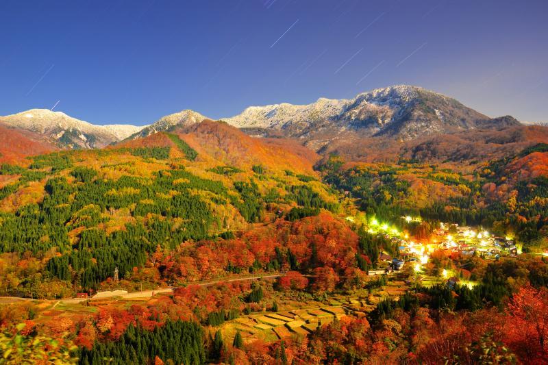 [ 月夜の冠雪 ]  月明かりに照らされた苗場山と秋山郷の集落の灯りが幻想的。