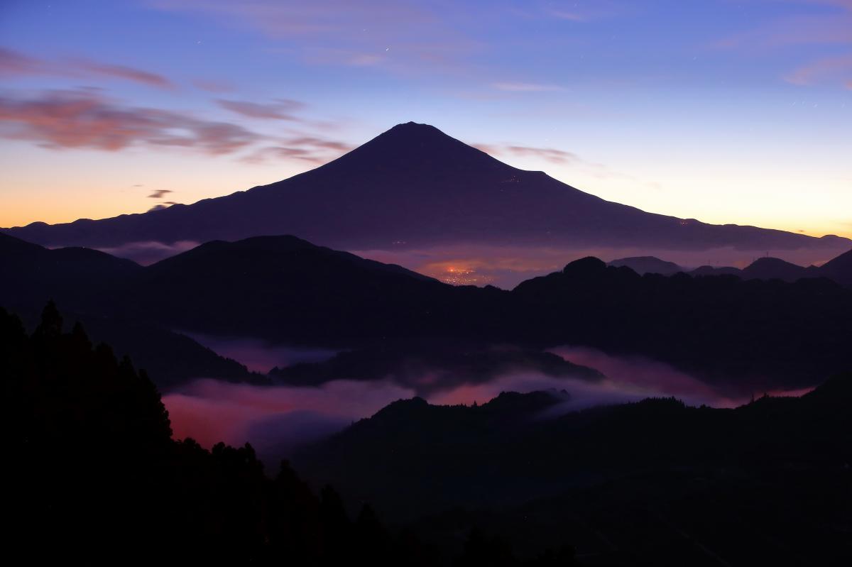 富士山と街あかりで輝く雲海 美しい富士山のシルエット。薄い雲海は街あかりが透けて幻想的な光景になります。