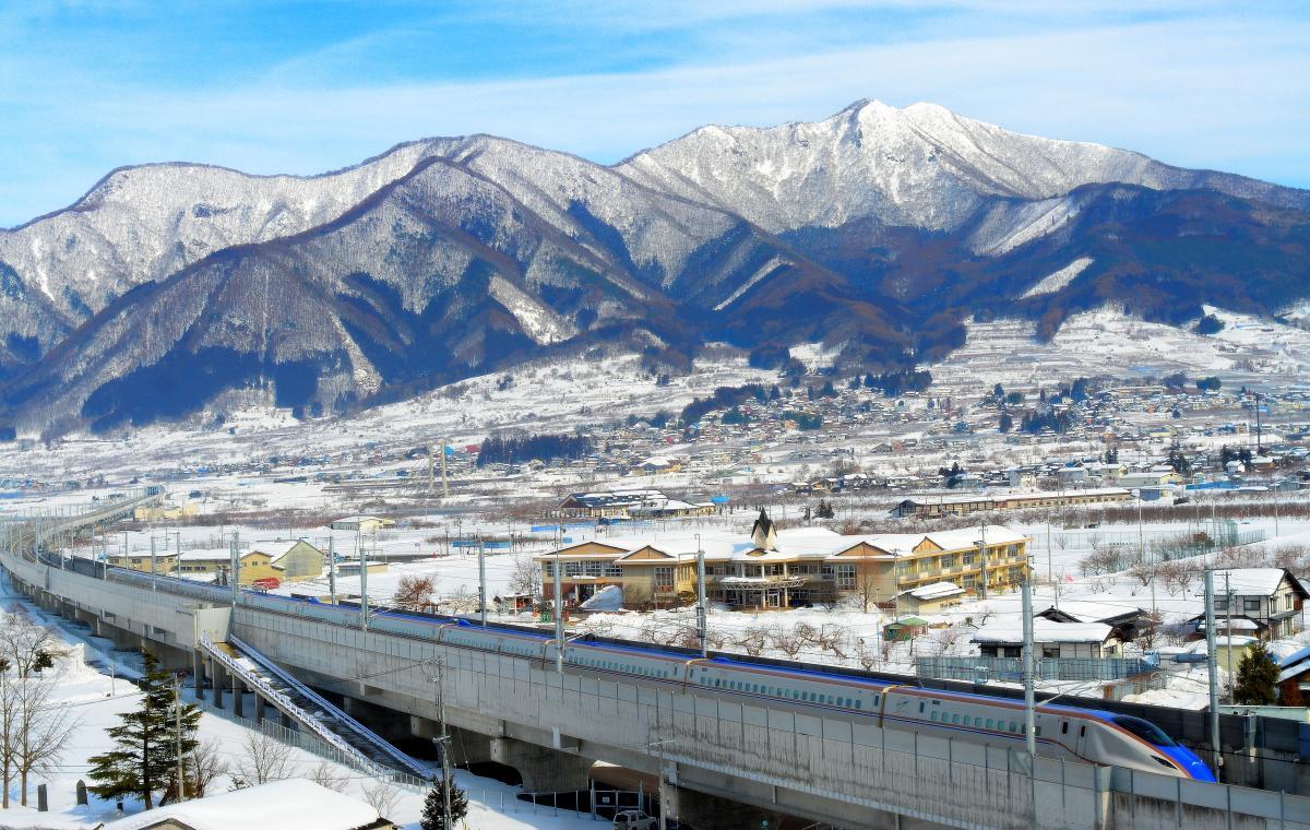 高丘トンネル 冬景色の中を駆け抜ける北陸新幹線と高社山
