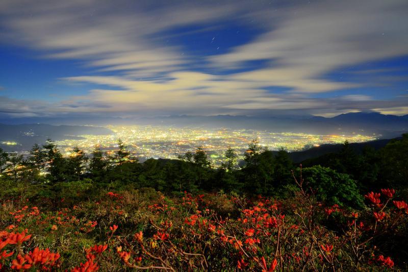 甲府盆地の大パノラマ夜景| 目映い街灯りに照らされ空を流れる雲が幻想的。広角レンズを使用。