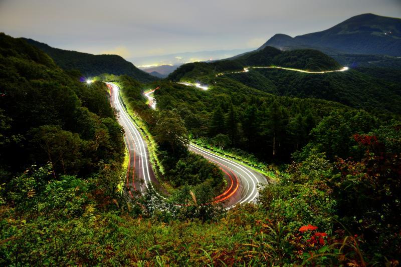 ヘアピンカーブ 磐梯吾妻スカイラインを走行する車の光跡。樹林帯・火山帯を走る観光道路で景観が素晴らしい「日本の道100選」に選定。