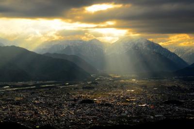 降り注ぐ光| 北アルプスと雲の隙間から街に光芒が降りてきました。